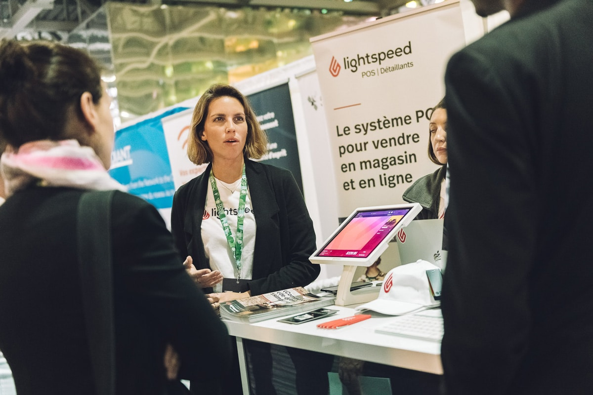 Woman speaking at an exhibitor booth at TAG